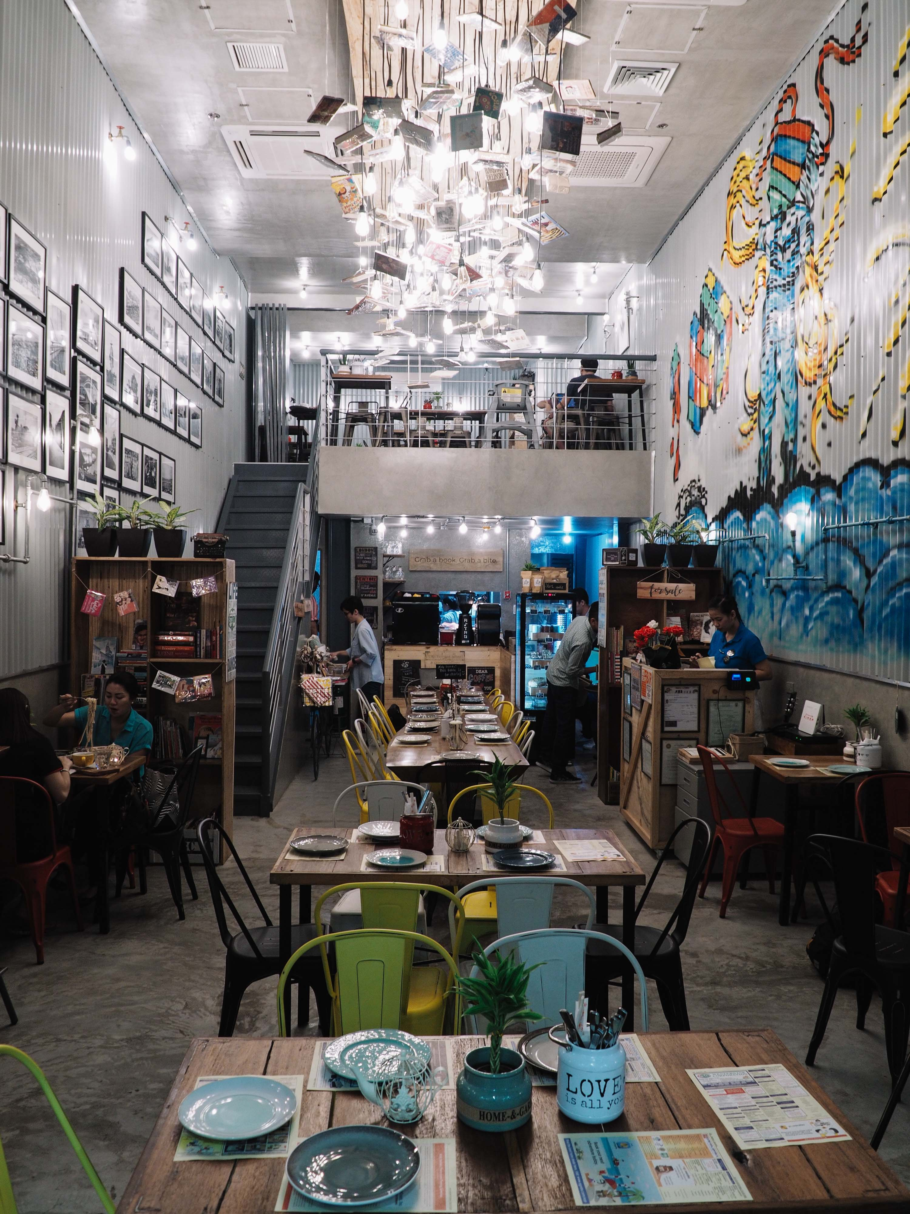 Buku-Buku Kafe's walls are similar to that of a trailer truck with graffiti and photographs hung on them.